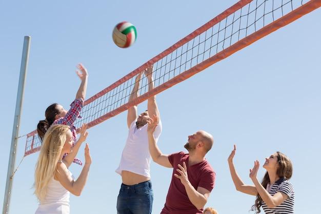 Vrienden die volleyball spelen bij strand