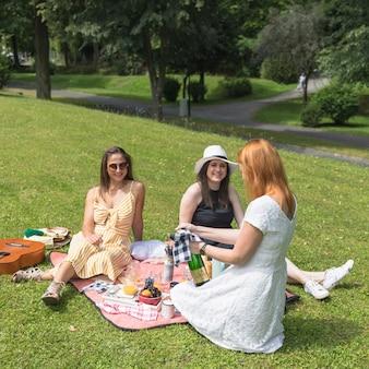 Vrienden die vrouw bekijken die de bierfles openen op picknick