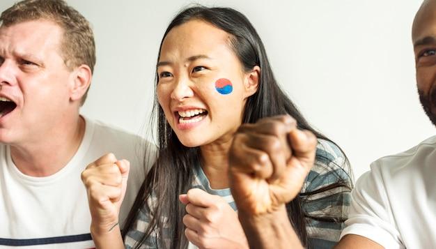 Vrienden die wereldbeker met geschilderde vlag toejuichen