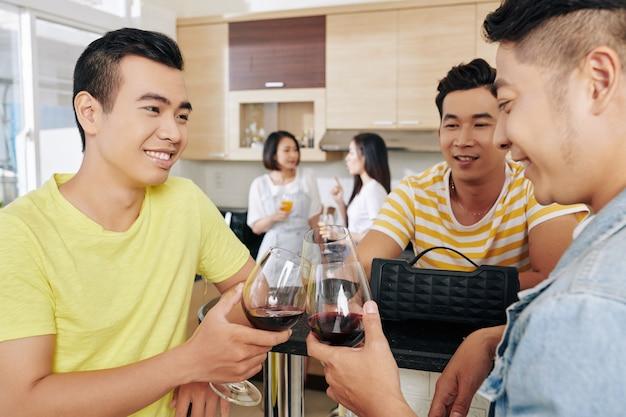 Vrienden die wijn drinken op feestje