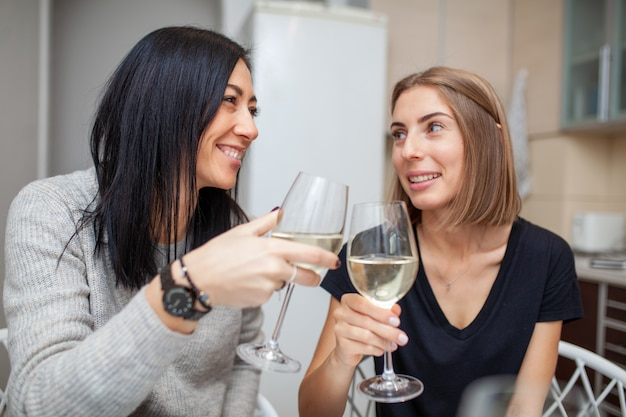 Vrienden die wijn en cake in de moderne stijlkeuken samenkomen. jonge vrouwen glimlachen en grappen met glazen wijn in zijn handen