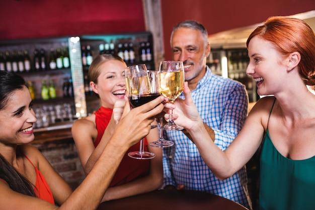 Vrienden die wijnglas in nachtclub roosteren