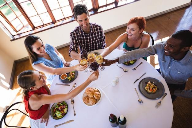 Vrienden die wijnglas roosteren bij lijst in restaurant