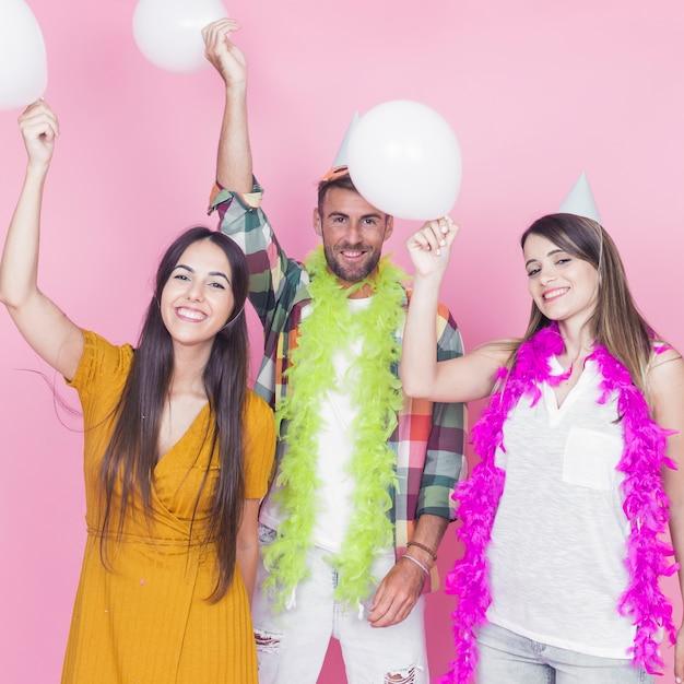 Vrienden die witte ballons houden die zich tegen roze achtergrond bevinden