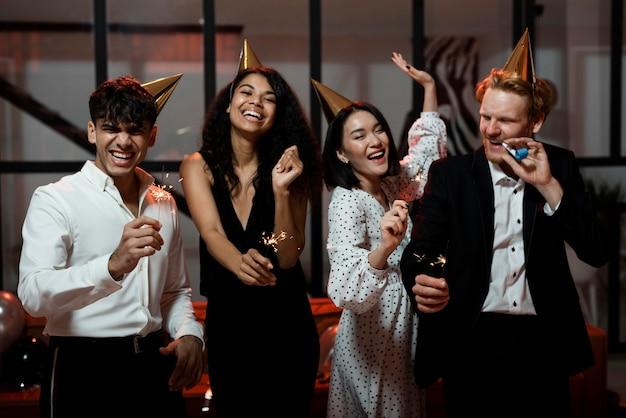Vrienden die wonderkaarsen houden op oudejaarsavondfeest