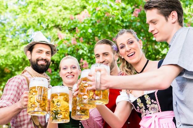 Vrienden die zich onder kastanje het roosteren met bier bevinden