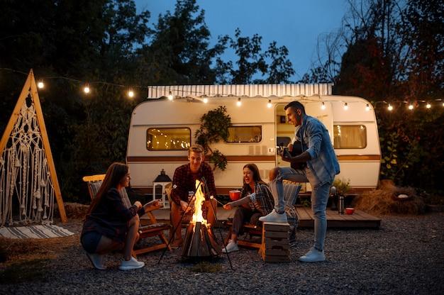 Vrienden die zich opwarmen bij het vuur, picknicken op kamperen in het bos