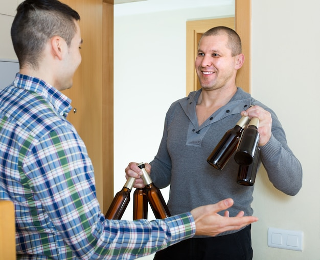 Vrienden die zich thuis verzamelen om bier te drinken