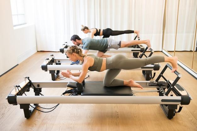 Vrienden doen pilates knielende bilspieren oefeningen