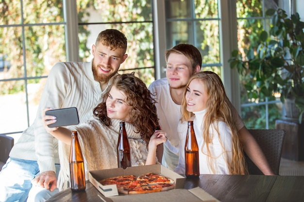 Vrienden drie twee mannen en twee vrouwen jonge volwassenen mooi en gelukkig samen met mobiel