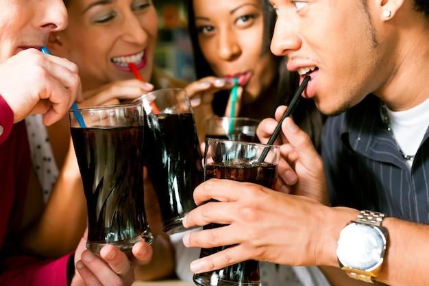 Vrienden drinken frisdrank in een bar