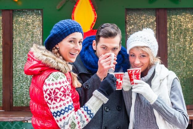 Vrienden drinken glühwein op kerstmis gemarkeerd