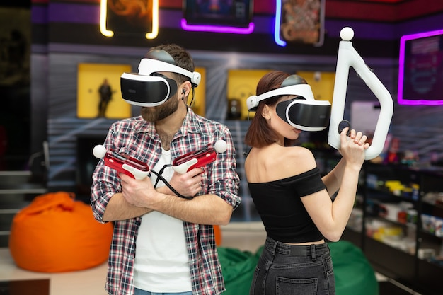 Vrienden, een man en een vrouw gebruiken een virtual reality-headset met bril en handbewegingscontrollers en wapens in de speelruimte.