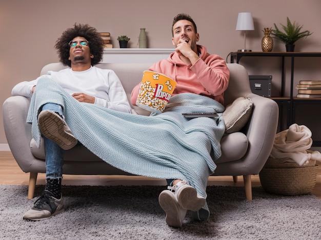 Vrienden eten popcorn en kijken naar film