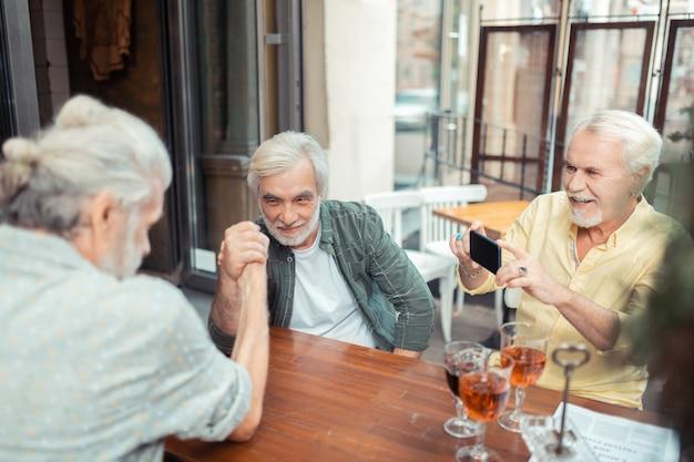 Vrienden filmen. grijsharige bejaarde gepensioneerde man filmt het armworstelen van zijn vrienden