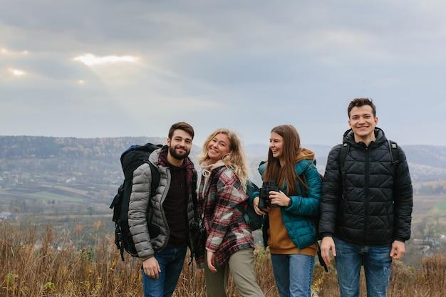 Vrienden genieten van de zonnestralen die door de wolken in de bergen schijnen