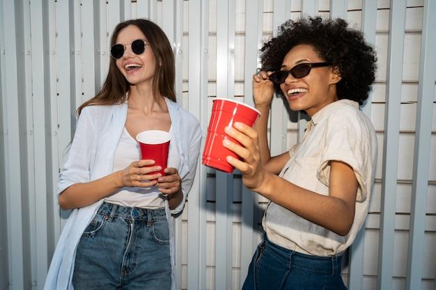 Vrienden genieten van drankjes uit plastic bekers