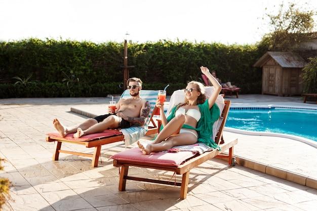 Vrienden glimlachen, cocktails drinken, liggend op ligstoelen bij het zwembad