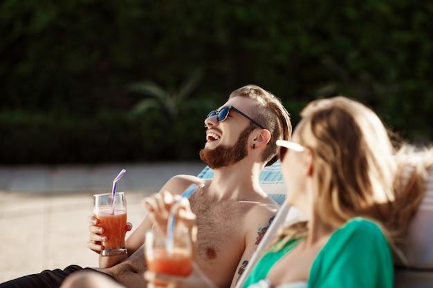 Vrienden glimlachen, cocktails drinken, liggend op ligstoelen bij zwembad