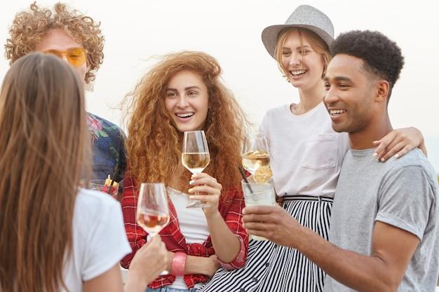 Vrienden glimlachen en wijn drinken terwijl ze elkaar omhelzen