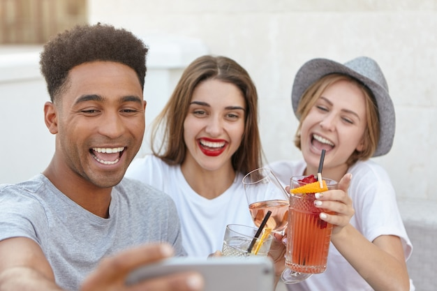 Vrienden glimlachen naar de camera van de mobiele telefoon tijdens het nemen van selfie