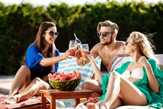 Vrienden glimlachen, watermeloen eten, cocktails drinken, ontspannen bij het zwembad