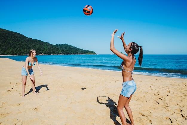 Vrienden gooien bal op het strand