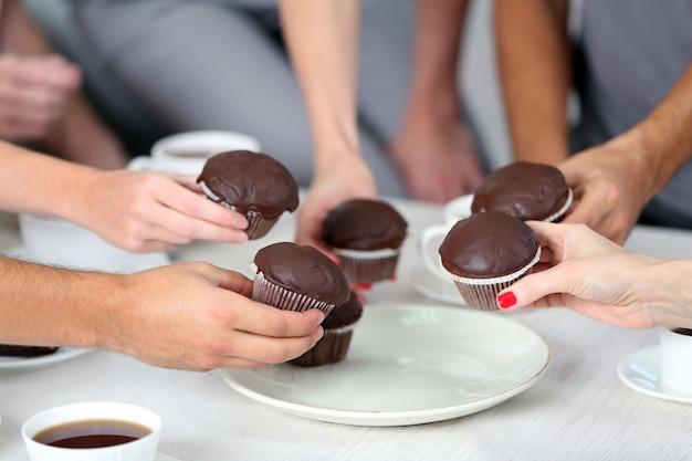 Vrienden handen met desserts en kopjes thee, close-up