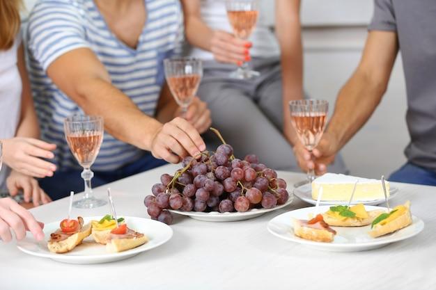 Vrienden handen met glazen wijn en snacks, close-up