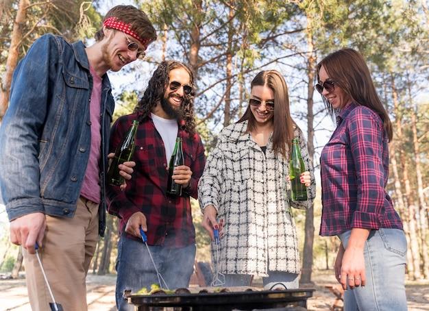 Vrienden hebben een barbecue buiten terwijl ze bier drinken
