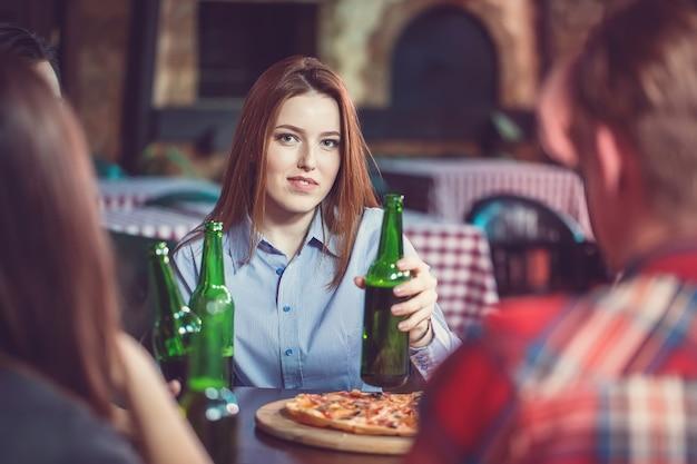 Vrienden hebben een drankje in een bar, ze zitten aan een houten tafel met bier en pizza. focus op een prachtig meisje dat haar fles aanraakt.