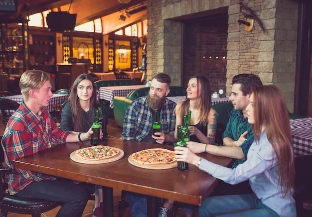 Vrienden hebben een drankje in een bar, ze zitten aan een houten tafel met bier en pizza.
