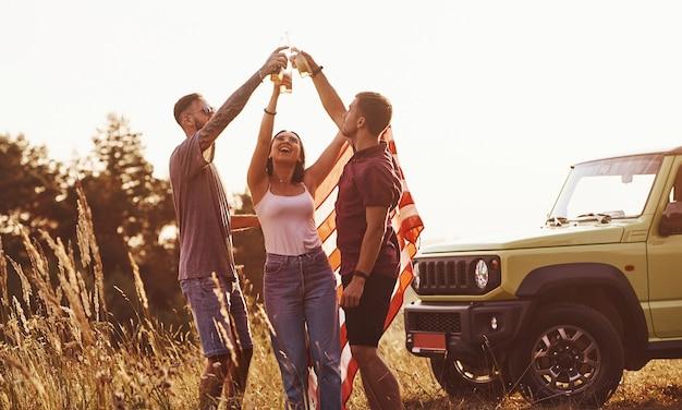 Vrienden hebben een leuk weekend buiten in de buurt van hun groene auto met amerikaanse vlag