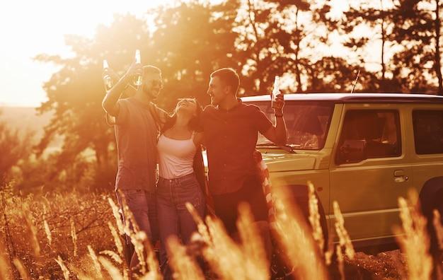 Vrienden hebben een leuk weekend buiten in de buurt van hun groene auto