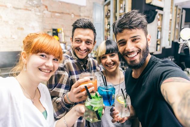 Vrienden hebben plezier in een bar met cocktails en nemen selfies