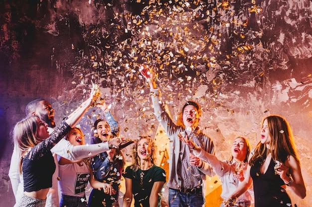 Vrienden hebben plezier in het vallen van confetti