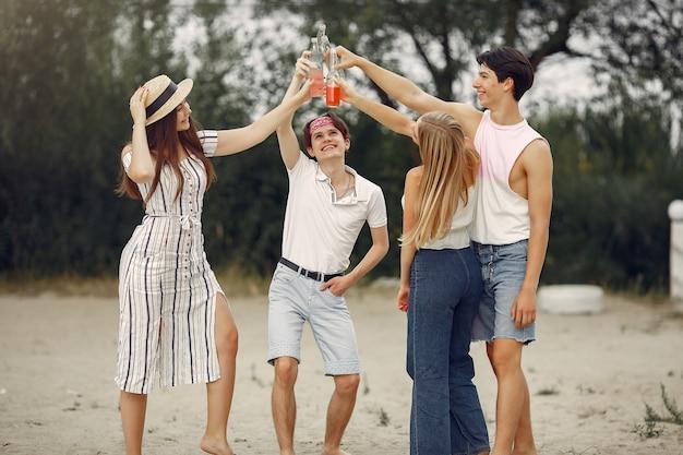 Vrienden hebben plezier op een strand met drankjes