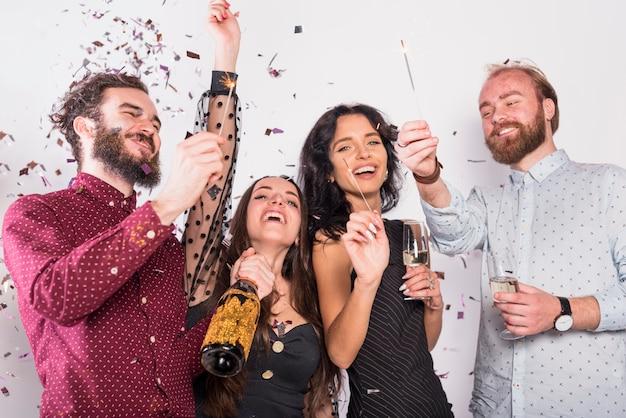 Vrienden hebben plezier op feestje met bengaalse lichten