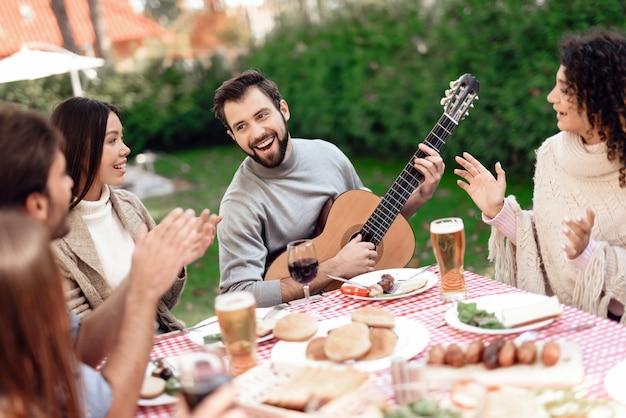 Vrienden hebben plezier, ze koken voedsel, drinken alcohol.