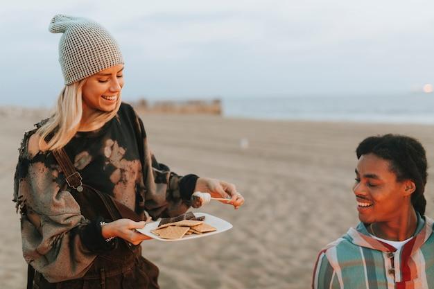 Vrienden hebben s'mores op het strand