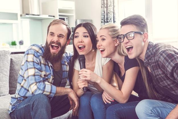 Vrienden hebben samen een feestje binnenshuis en zingen karaoke