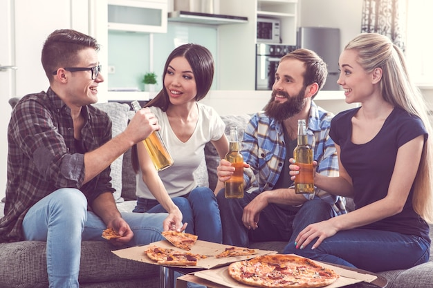 Vrienden hebben samen een feestje binnenshuis pizza eten
