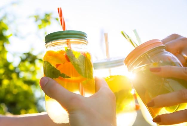 Vrienden houden verse limonade in pot met stro. hipster zomerfeest met drankjes. gezonde veganistische levensstijl. milieuvriendelijk in de natuur. citroenen, sinaasappelen en bessen met munt in het glas.