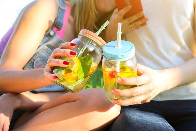 Vrienden houden verse limonade in potten met rietjes. hipster zomerfeest met drankjes. gezonde veganistische levensstijl. milieuvriendelijk in de natuur. citroenen, sinaasappelen en bessen met munt in het glas.