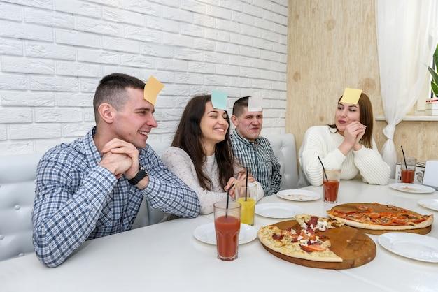 Vrienden in café die pizza eten en spelen, raad eens wie