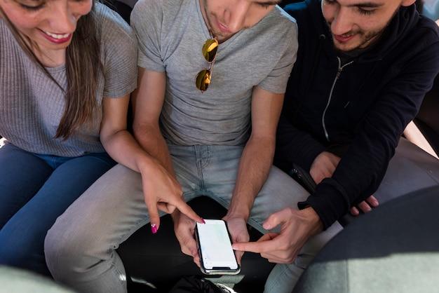 Vrienden in de auto kijken op de navigatiesysteem