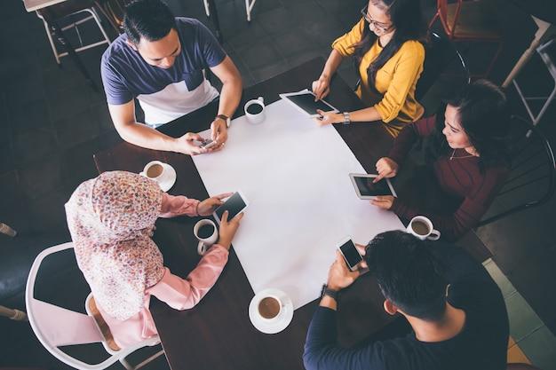 Vrienden in een restaurant met alle mensen aan tafel bezig met hun eigen digitale apparaten