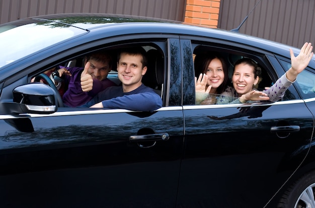 Vrienden in een zwarte auto die in roeping gaan