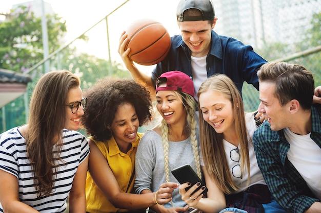 Vrienden in het park die millennial smartphones en jeugdcultuurconcept gebruiken