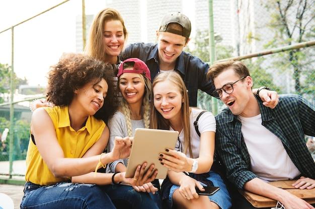 Vrienden in het park met behulp van een digitale tablet millennial en jeugdcultuur concept